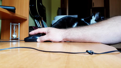 Hand of a Caucasian man working with the mouse on a wooden table, remote work, freelancer, workplace Live Action