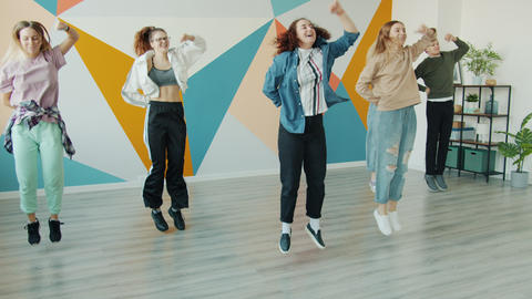 Slow motion of joyful teens dancing in contemporary dance studio jumping moving ライブ動画
