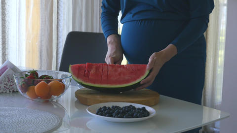 Young pregnant woman cuts watermelon ライブ動画
