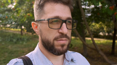 serious guy with beard and glasses talks standing in park ライブ動画
