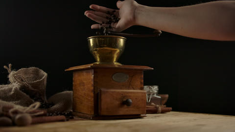 Woman's hand throws coffee beans into vintage coffee mill for grinding. Wooden Live Action