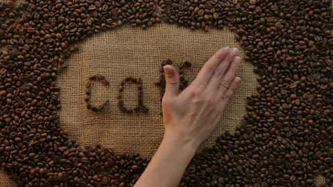 Lettering italian word caffe- coffee made of coffee beans on burlap.Elegant hand Live Action