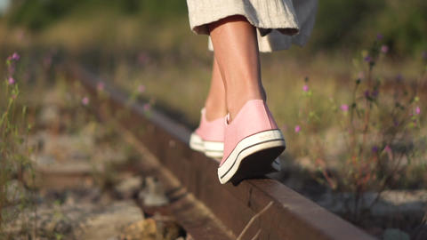 Girl walking along railroad rail. Romantic slow motion tracking shot of young Live Action