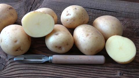 Potatoes on the wood board. Fresh potato on rustic background ライブ動画