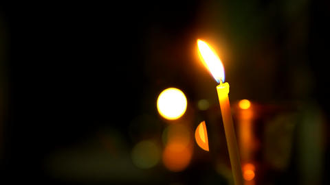 One burning Church candle close-up on the dark background Acción en vivo