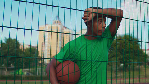 Athlete with basketball leaning on sports fence GIF