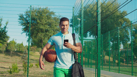 Sportsman with phone walking on court before game GIF