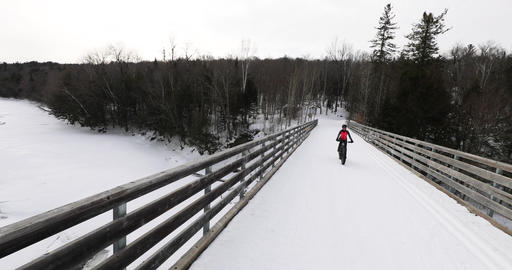 Fat bike in winter. Fat biker riding bicycle in the snow in winter. Woman living Live Action