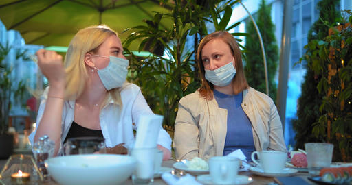daughter and mother take off blue face masks sitting at restaurant table GIF