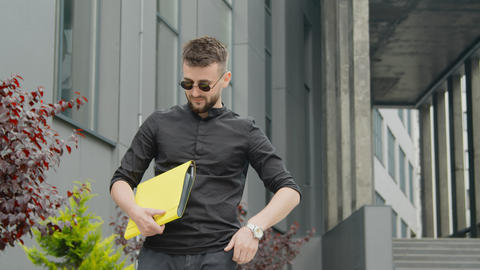 Businessman with glasses and a yellow folder with documents waiting for a ライブ動画