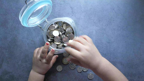 Top view of baby child saving coins in a jar ライブ動画