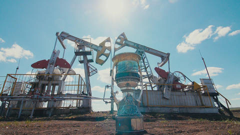 cup with Yuri Gagarin portrait on oil field with pump jacks GIF