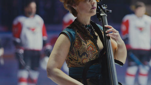 woman in elegant dress plays cello against hockey players GIF
