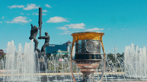 cup with Yuri Gagarin near fountain against workers statue GIF
