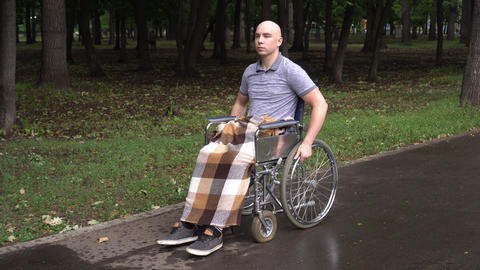 A young man with oncology rides a wheelchair through the park. The man is bald Live Action