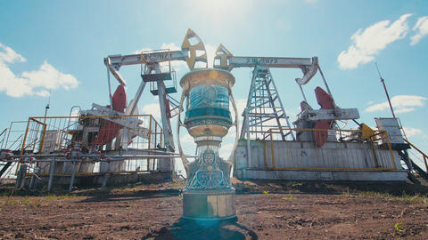 sports cup on oil field against pump jacks under blue sky GIF