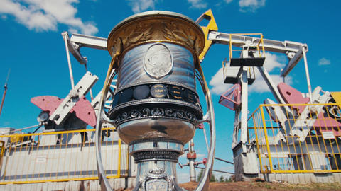 elegant cup with Yuri Gagarin portrait stands on oil field GIF