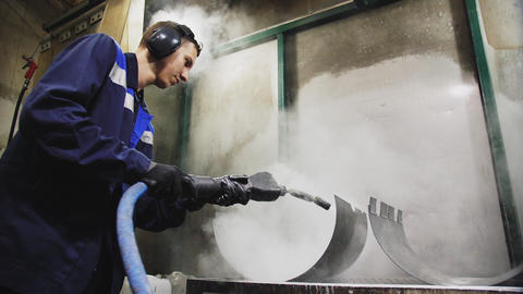 employee works with hot steam jet to clean metal parts close GIF