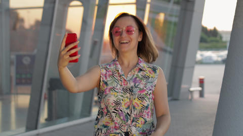 Tourist girl wearing trendy sunglasses uses phone. Using smartphone for call ライブ動画