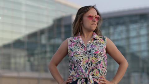 Angry mad woman tourist in trendy sunglasses raising fists, looking at camera Live Action