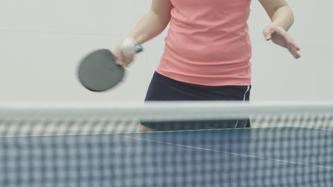 Unrecognizable woman hitting ball with racket over table tennis net. Young Acción en vivo