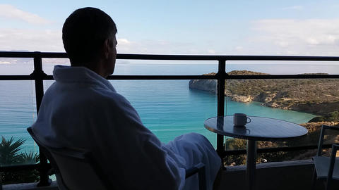 Sitting with his back to the man on the balcony with sea views Footage