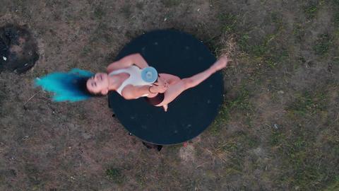 Pole dance on the field - woman with long blue braids dancing the dancing pole - Acción en vivo