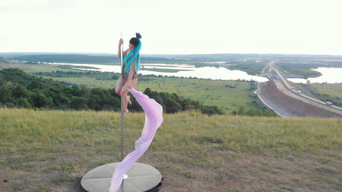 Woman with blue braids holding by the pole and waving with pink veil Acción en vivo