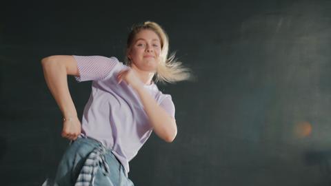 Active young woman rehearsing modern hip-hop dance in dark art studio Acción en vivo
