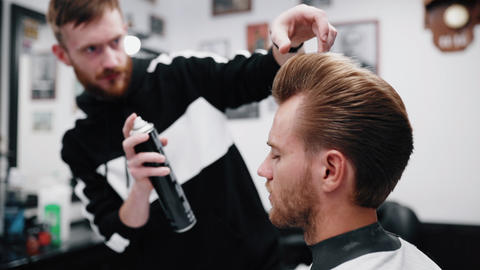 Stylish men's haircut. Barber makes hair styling special varnish Live Action