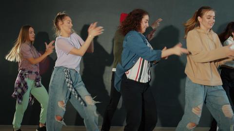 Group of students dancing in dark dancehall performing creative dance show Acción en vivo