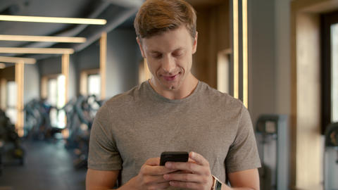 Cheerful bodybuilder standing at gym. Sportsman texting message in sport club Acción en vivo