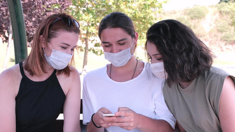 Group of friends wearing face masks watching a video on a smartphone. Millennials having fun GIF