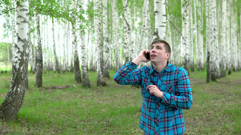 A young man is looking for a cellular network in a birch forest. A man is Live Action