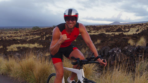 Triathlon biking - male triathlete cycling giving Hawaiian shaka hand sign Acción en vivo