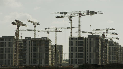 Large construction site with many cranes working over buildings GIF