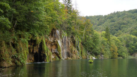 Rocky lakeside with waterfall and green trees. Cloudy day at Plitvice Lakes GIF