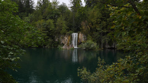 Waterfall falls into Plitvice Lake. Scenery landscape of cloudy forest around GIF