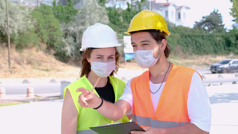 Portrait of worker and engineer wearing face masks checking production process and discussing GIF