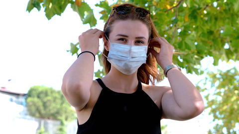 Portrait of a young woman puts on a medical mask and looks at the camera, Outdoors shooting. GIF