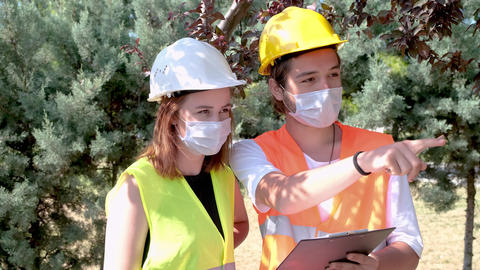 Portrait of worker and architect wearing face masks checking landscaping design and discussing GIF