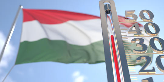 Thermometer shows high air temperature against blurred flag of Hungary. Hot Photo