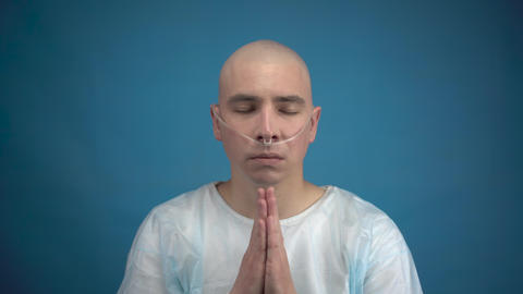Bald young man with oncology looks at the camera and prays on a blue background Acción en vivo