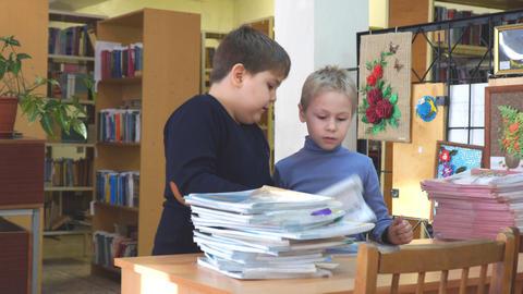 Two elementary school students standing at a Desk rearrange books Acción en vivo