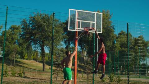 Streetball player making slam dunk over defender GIF