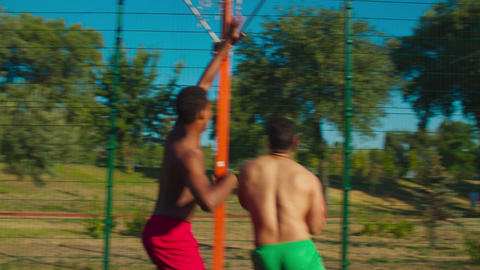 Two shirtless friends playing basketball on court GIF