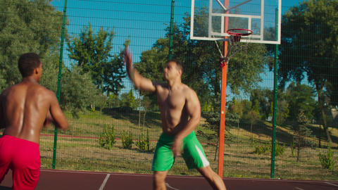 Shirtless streetball player making step back shot GIF