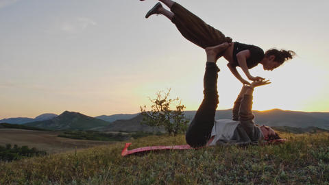 Couple practice complex exercises of yoga at dusk on the hilltop GIF