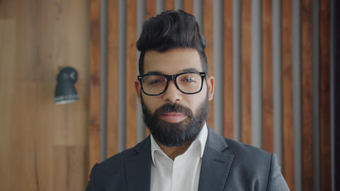 Portrait of handsome Middle Eastern man wearing glasses and suit standing Acción en vivo