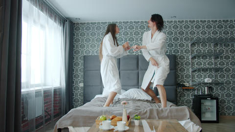 Slow motion of joyful youth girl and guy dancing on hotel bed relaxing having Live Action